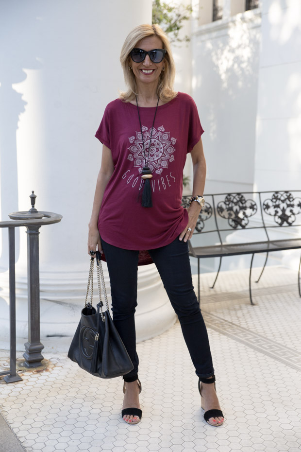 burgandy womens soft rayon t shirt with good vibes print worn with black jeans