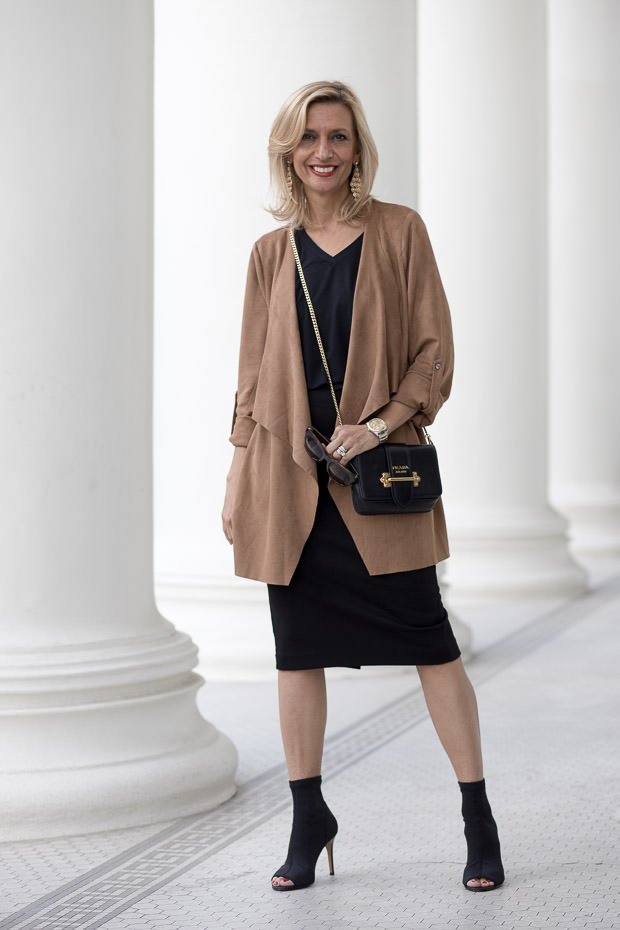 A Holiday Party Look in Black and gold with a tan cascading collar jacket